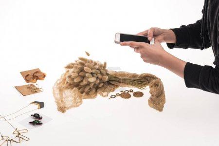 Photo pour Crochet vue du photographe prenant des photos de composition avec flore et bijoux sur smartphone sur blanc - image libre de droit