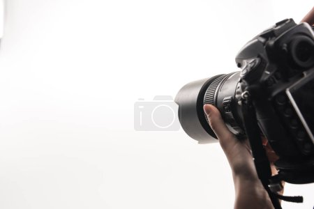 Photo for Cropped view of photographer working with digital camera isolated on white - Royalty Free Image
