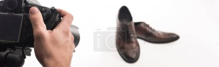 Photo for Partial cropped view of male photographer making commercial photo shoot of male shoes on white, panoramic shot - Royalty Free Image
