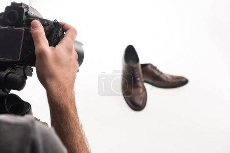 Photo pour Vue recadrée du photographe masculin faisant séance photo commerciale de chaussures masculines sur blanc - image libre de droit