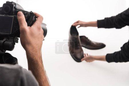 Photo pour Vue recadrée de photographes commerciaux faisant séance photo de chaussures masculines sur blanc - image libre de droit