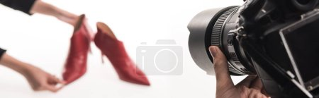 Photo for Cropped view of photographers making commercial photo shoot of female red heel shoes on white, panoramic shot - Royalty Free Image