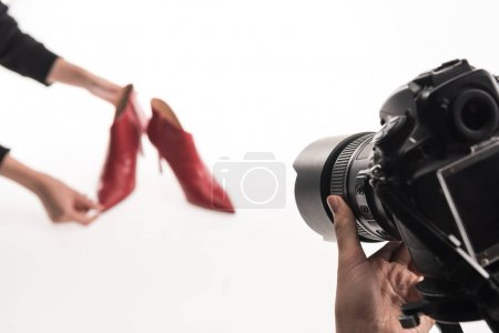 Photo for Cropped view of commercial photographers making commercial photo shoot of female red heel shoes on white - Royalty Free Image
