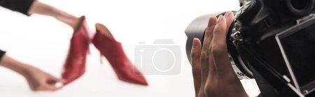 Photo pour Vue recadrée de photographes commerciaux faisant une séance photo commerciale de chaussures à talons rouges féminines sur blanc, vue panoramique - image libre de droit