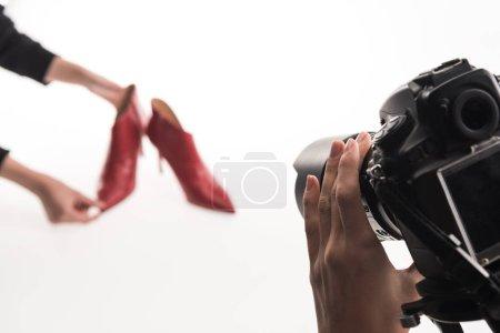 Photo pour Vue recadrée de photographes faisant séance photo commerciale de chaussures à talons rouges féminines sur blanc - image libre de droit