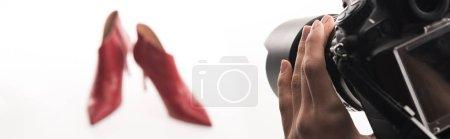 Photo pour Vue recadrée du photographe faisant une séance photo commerciale de chaussures à talons rouges féminines sur blanc, plan panoramique - image libre de droit