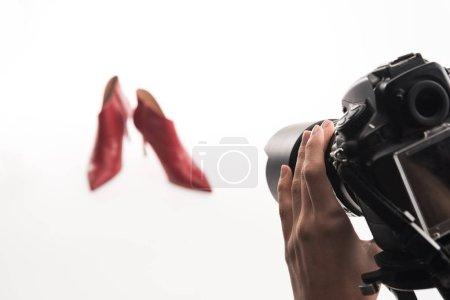 Photo pour Vue recadrée de photographe femelle faisant séance photo commerciale de chaussures à talons rouges féminines sur blanc - image libre de droit