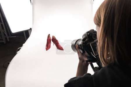 Photo for Cropped view of commercial photographer making commercial photo shoot of female red heel shoes on white - Royalty Free Image