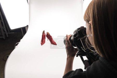 Photo pour Photographe faisant séance photo commerciale de chaussures à talons rouges féminines sur blanc - image libre de droit