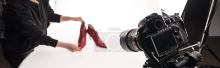 Photo for Cropped view of commercial photographer making commercial photo shoot of female red heel shoes on white, panoramic shot - Royalty Free Image