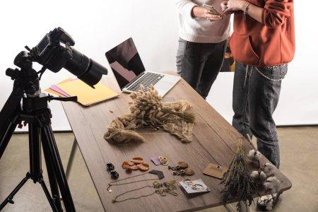 Photo pour Vue recadrée de deux photographes commerciaux travaillant avec des accessoires, appareil photo numérique, ordinateur portable et smartphone - image libre de droit