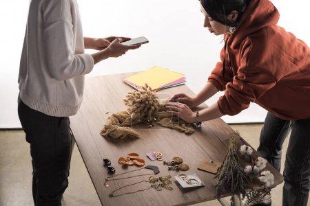 Foto de Dos fotógrafos comerciales que toman fotos de composición con flora y joyas en teléfonos inteligentes - Imagen libre de derechos