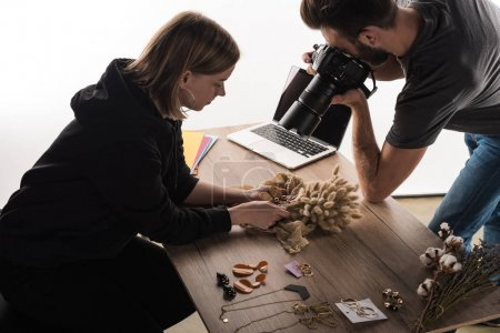 Photo for Two commercial photographers take picture of composition with flora and jewelry on digital camera - Royalty Free Image