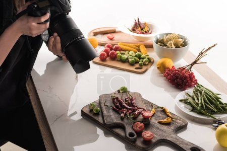 Photo for Cropped view of female photographer making food composition for commercial photography and taking photo on digital camera - Royalty Free Image