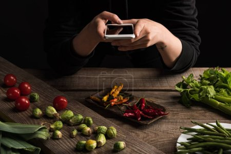 Photo for Cropped view of professional photographer making food composition for commercial photography on smartphone on wooden table - Royalty Free Image
