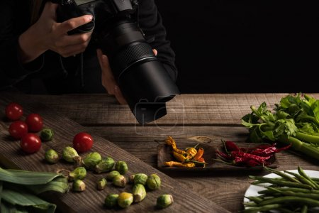 cropped view of female photographer making food composition for commercial photography and taking photo on digital camera