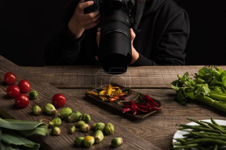 Photo for Cropped view of female photographer making food composition for commercial photography and taking photo on digital camera on wooden table - Royalty Free Image