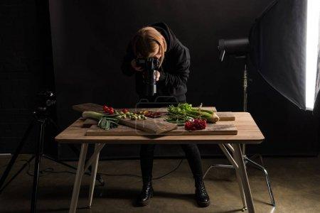 Foto de Fotógrafa femenina que elabora composición de alimentos para fotografía comercial y toma fotos en cámaras digitales - Imagen libre de derechos