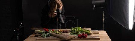 Foto de Fotógrafo profesional haciendo composición de alimentos para fotografía comercial y tomando fotos en cámara digital, disparo panorámico. - Imagen libre de derechos