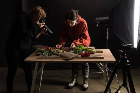 Photo pour Deux photographes préparent des aliments pour la photographie commerciale et prennent des photos sur un appareil photo numérique - image libre de droit