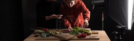 Photo for Cropped view of two photographers making food composition for commercial photography on smartphone, panoramic shot - Royalty Free Image