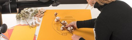 cropped view of photographer making composition with cotton flower and jewelry for photo shooting, panoramic shot