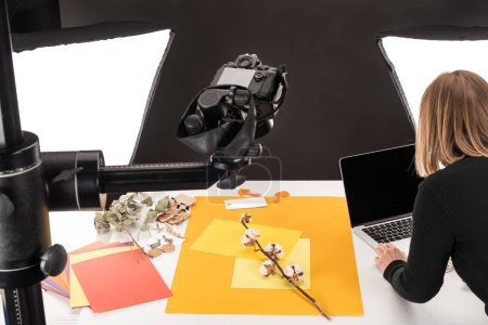 Photo for Photographer making composition with cotton flower and accessories for photo shooting - Royalty Free Image