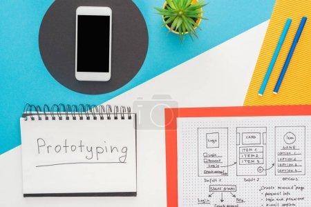 Photo pour Vue du haut du smartphone près du modèle de conception de site Web et ordinateur portable avec lettrage prototypage sur fond abstrait - image libre de droit