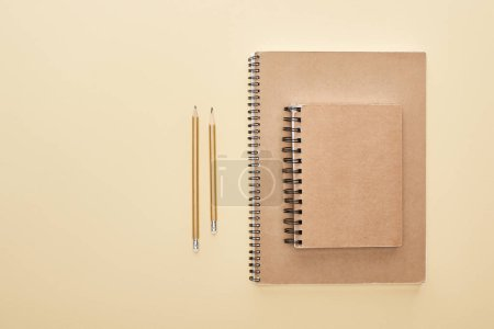 flat lay with paper blank notebooks with pencils on beige background