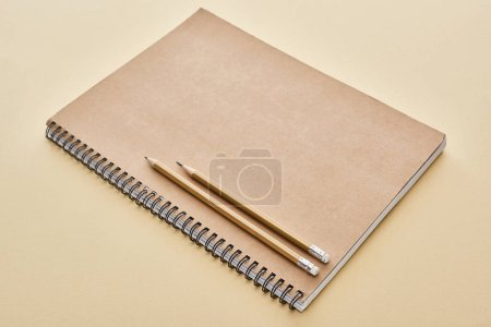 Photo for Paper blank notebook with pencils on beige background - Royalty Free Image