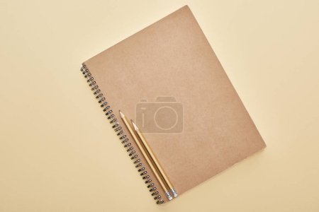 Photo for Top view of  paper blank notebook with pencils on beige background - Royalty Free Image