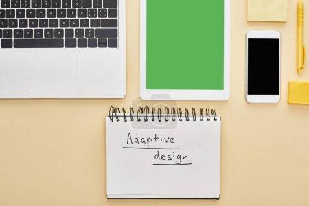 Photo pour Planche à plat avec gadgets et lettrage adaptatif dans un bloc-notes sur fond jaune - image libre de droit