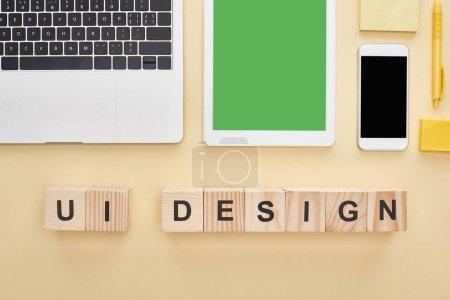 Photo pour Pose plate avec des gadgets et des blocs de bois avec lettrage ui design sur fond jaune - image libre de droit