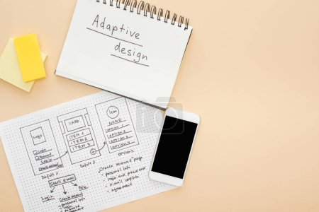 Photo pour Top view of smartphone near website design template and notebook with adaptive design lettering on beige background - image libre de droit