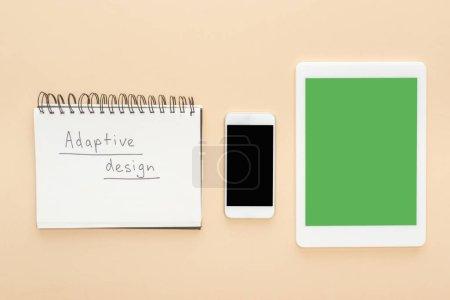 Photo pour Planche à plat avec gadgets près d'un cahier à dessin adaptatif lettrage sur fond beige - image libre de droit