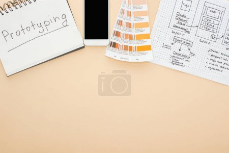 Photo pour Top view of smartphone near website design template, color palette and notebook with prototyping lettering on beige background - image libre de droit