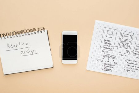 Photo for Top view of smartphone near website design template and notebook with adaptive design lettering on beige background - Royalty Free Image