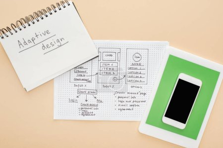 Photo pour Top view of gadgets near website design template and notebook with adaptive design lettering on beige background - image libre de droit