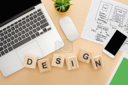 top view of gadgets near wooden blocks with design lettering, website design template and green plant on beige background