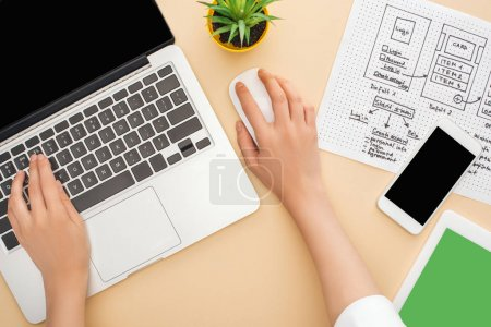 Photo for Partial view of designer using laptop near gadgets, website design template and green plant on beige background - Royalty Free Image