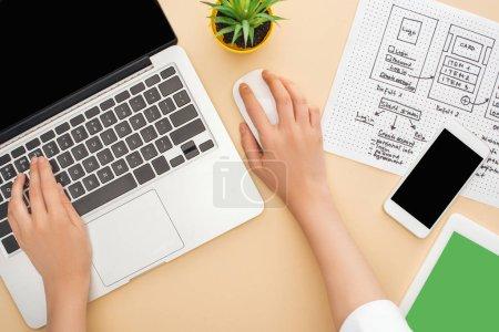 Photo pour Vue partielle du concepteur à l'aide d'un ordinateur portable près de gadgets, modèle de conception de site Web et plante verte sur fond beige - image libre de droit