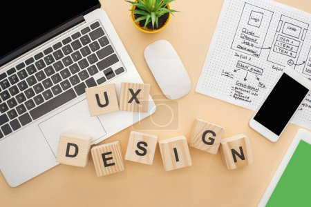 Photo for Top view of gadgets near wooden blocks with ux design lettering, website design template and green plant on beige background - Royalty Free Image