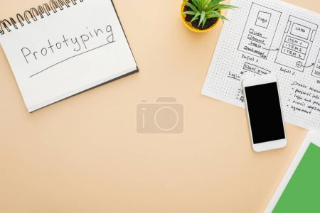 Photo for Top view of gadgets near website design template, notebook with prototyping lettering and green plant on beige background - Royalty Free Image