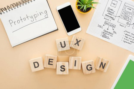 Photo pour Top view of gadgets near wooden blocks with ux design lettering, website design template, notebook with prototyping lettering and green plant on beige background - image libre de droit