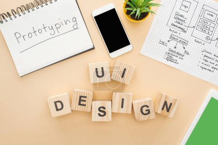 Photo for Top view of gadgets near wooden blocks with ui design lettering, website design template, notebook with prototyping lettering and green plant on beige background - Royalty Free Image