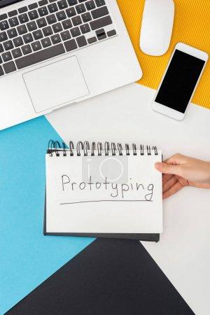 Photo pour Vue en coupe d'une femme tenant un bloc-notes avec prototypage de lettres près d'un ordinateur portatif, d'un téléphone intelligent, d'une souris d'ordinateur sur fond géométrique abstrait - image libre de droit