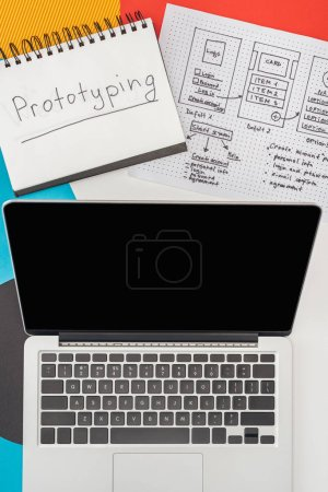 Photo pour Top view of notebook with prototyping lettering, laptop and website design template on abstract geometric background. - image libre de droit