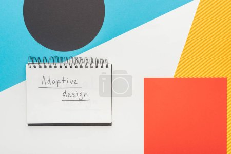 Photo pour Top view of notebook with adaptive design lettering on abstract geometric background - image libre de droit
