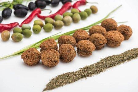 vista de cerca de aceitunas, chile, cebolla verde, hierba y falafel sobre fondo blanco
