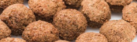 close up view of fresh cooked falafel balls on white background, panoramic shot